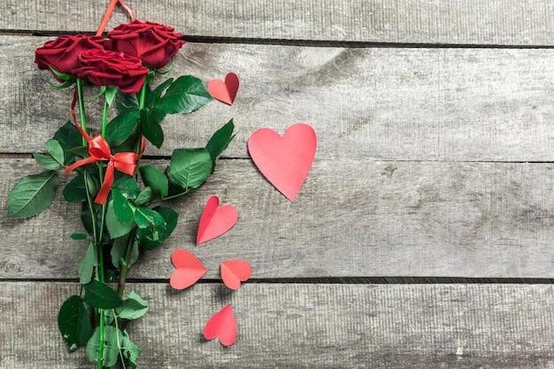 Rosen und herzen auf hölzernem brett, valentinstaghintergrund
