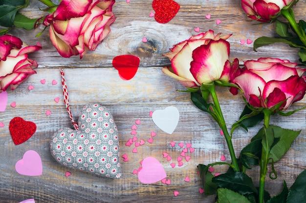 Rosen und herzen auf hölzernem hintergrund. valentinstag oder muttertagesgrußkarte