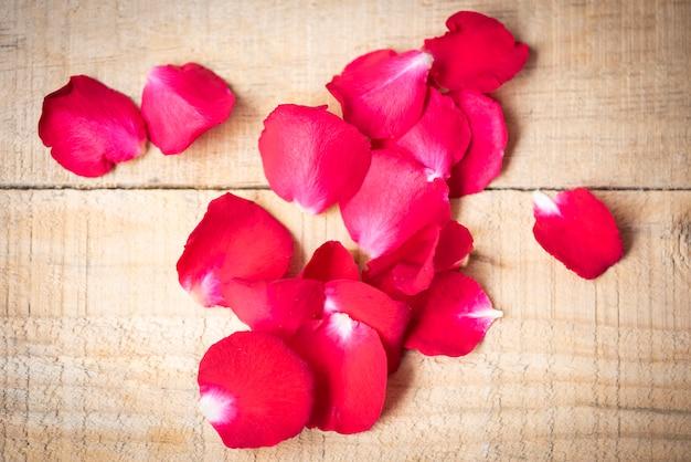 Rosenblätter auf hölzernem hintergrund, tonweinleseartklassiker - blühen sie rote rosafarbene blumenblätter für valentinstagkonzept