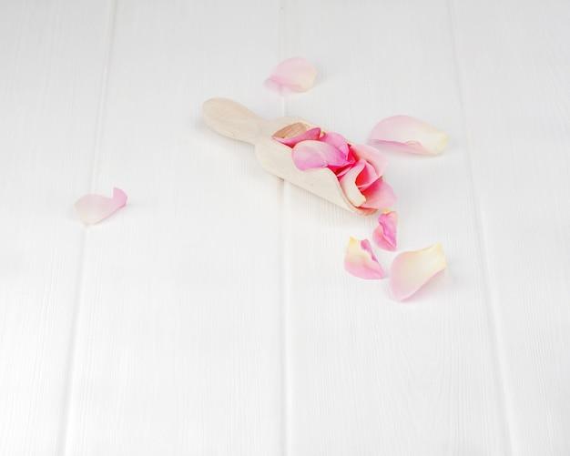 Rosenblätter auf weißen holztellern. nahansicht.