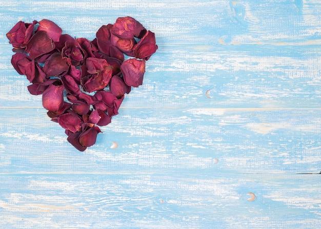 Rosenblätter in einer herzform auf dem weinleseholztisch.