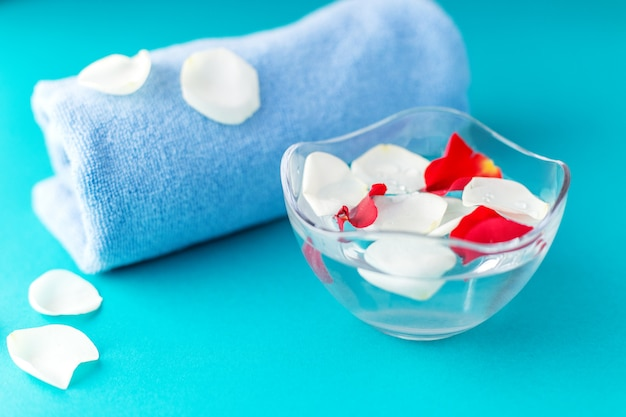 Rosenblätter in einer schüssel mit wasser und einem handtuch.