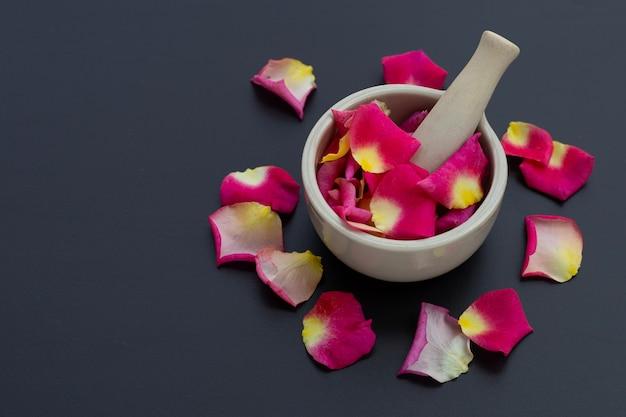 Rosenblätter in porzellanmörser mit stößel isoliert auf dunkler oberfläche.