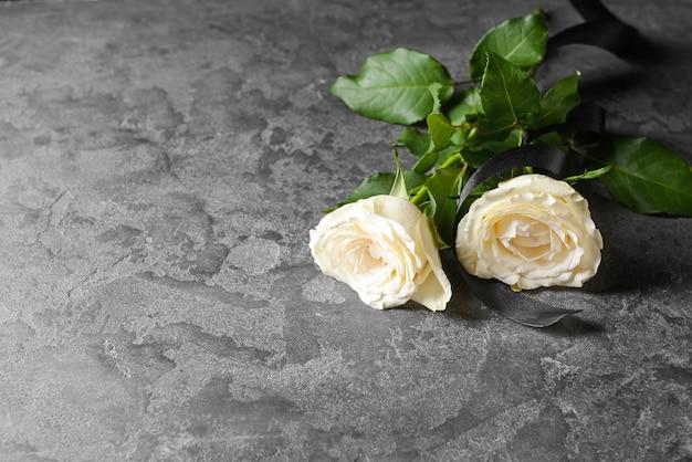 Rosenblüten und schwarzes trauerband auf grunge-tisch Premium Fotos