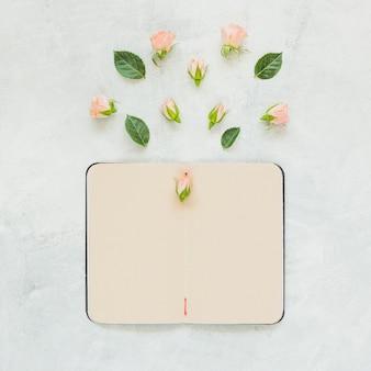 Rosenblume und -blätter über dem leeren notizbuch gegen konkreten hintergrund