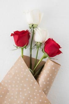 Rosenblumen im packpapier auf tabelle