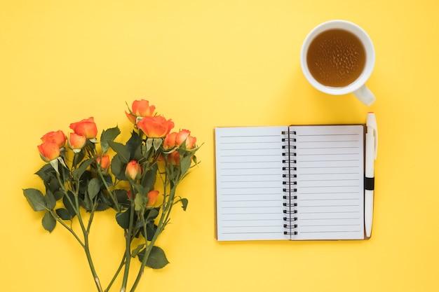 Rosenblumen mit notizbuch und tee auf tabelle