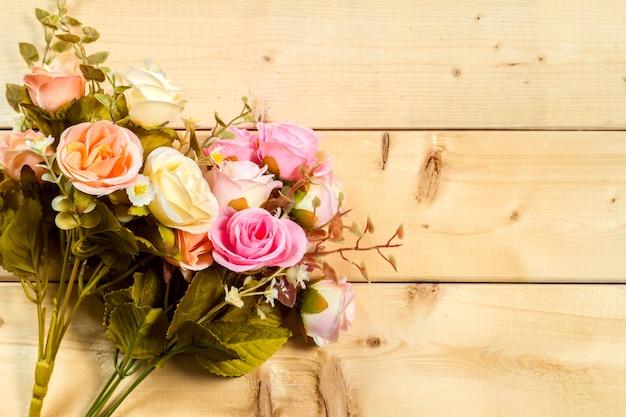 Rosenblumen und leerer raum auf hölzernem hintergrund
