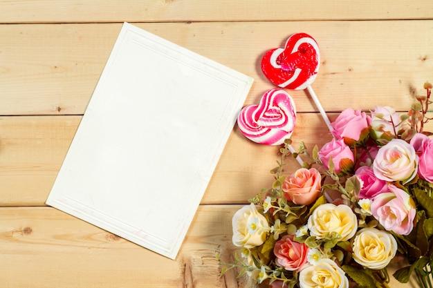Rosenblumen und leeres etikett für ihren text mit herzformbonbon auf hölzernem hintergrund