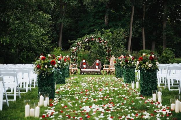 Rosenblumenblätter bedecken den grünen garten, der zu den traditionellen hindischen weddi bereit ist