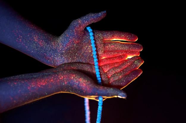 Rosenkranz in der hand, gebet. licht durch die handflächen in ultravioletten, gott und religion, perlen. göttliches licht durch deine finger