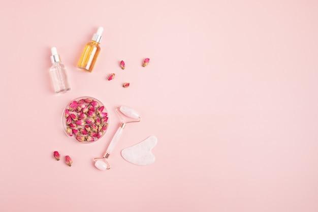 Rosenquarz-gesichtsroller, gua-sha-stein, ätherisches öl und trockene rosen. natürliches hautpflegekonzept. ansicht von oben, flach
