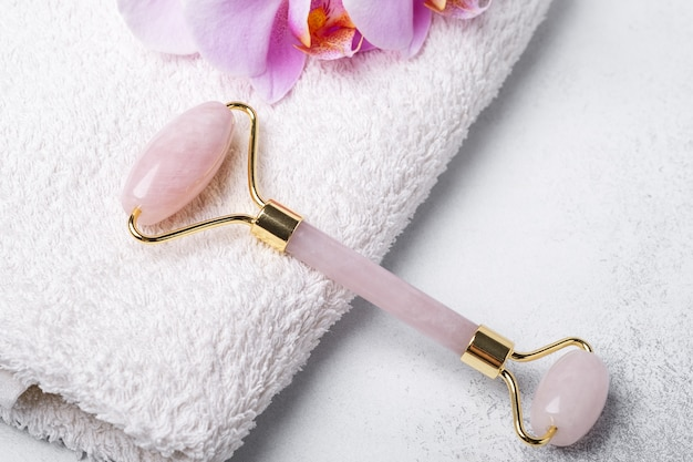 Rosenquarz-jadewalze und gua sha-massagegerät auf handtuch auf steinhintergrund. nahansicht. massagewerkzeug für die gesichtspflege, spa-schönheitsbehandlungskonzept