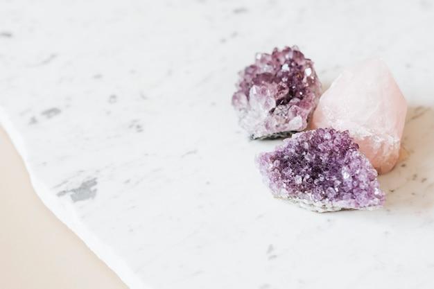 Rosenquarz und amethyst-heilkristalle auf einer marmor-arbeitsplatte