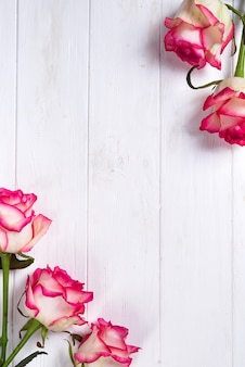 Rosenrahmen auf hölzernem weißem hintergrund