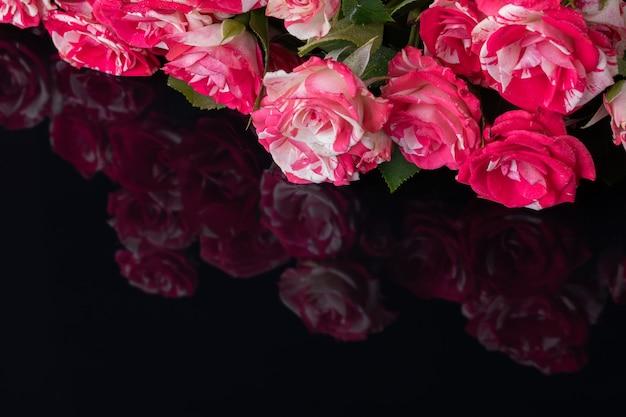 Rosenstrauß auf schwarzem hintergrund mit reflexionen von blumen von glänzender oberfläche.