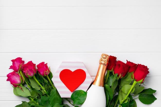 Rosenstrauß, flasche champagner und geschenkbox flach liegen