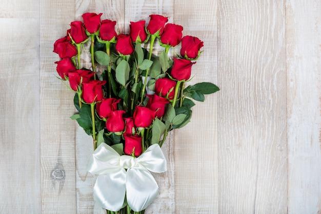 Rosenstrauß geformt von einem herzen mit einem bogen auf dem hölzernen hintergrund