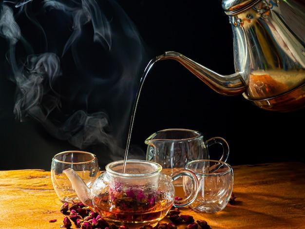 Rosenteeblätter im glas werden mit heißem wasser aus dem wasserkocher gebraut. auf holztisch und schwarzem farbhintergrund.