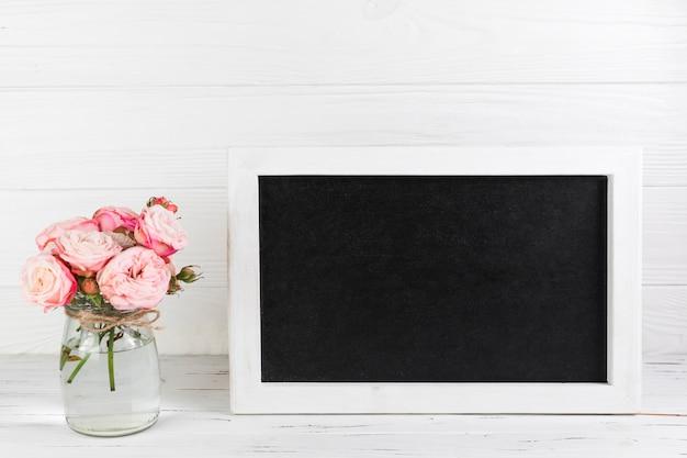 Rosenvase nahe dem leeren rahmen auf schreibtisch gegen weißen planke maserte hintergrund