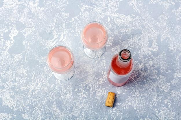 Roséwein-verkostungslayout. geöffnete flasche und zwei gläser mit roséwein auf grauem hintergrund.