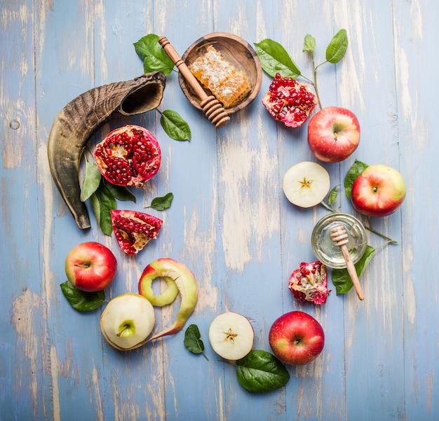 Rosh hashanah (hashana) - jüdisches neujahrsfeiertagskonzept. honigglas und frische äpfel mit granatapfel und schofarhorn auf blauem hintergrund. kopieren sie platz für text. sicht von oben