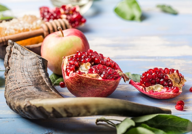 Rosh hashanah (hashana) - jüdisches neujahrsfeiertagskonzept. symbole: honigglas und frische äpfel mit granatapfel und schofarhorn auf blauem grund. kopieren sie platz für text. sicht von oben