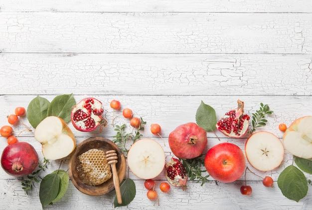 Rosh hashanah - jüdisches neujahrsfeiertagskonzept. traditionelle symbole: honigglas und frische äpfel mit granatapfel und schofarhorn
