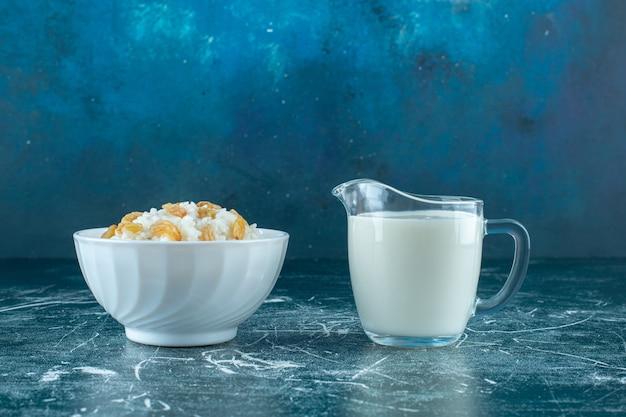 Rosinen auf einer schüssel milchreis neben einem glas milch auf blauem hintergrund. foto in hoher qualität