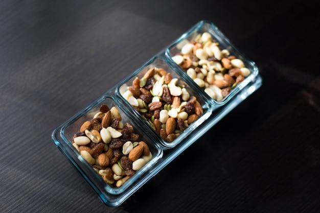 Rosinen, erdnüsse und pistazien in eleganten glasschalen