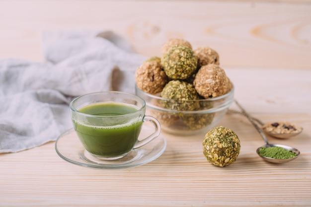 Rosinen mandelhonig glückskugeln. gesunde haferflocken-snacks energy balls mit hafer-mandel-butter und honig. tasse matcha-tee