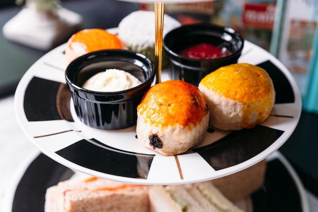 Rosinen-scone und einfacher scone auf schwarzweiss-farbplatte. mit marmelade und butter serviert.