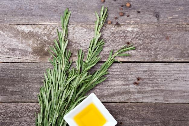 Rosmarin, olivenöl und pfeffer auf altem hölzernen hintergrund