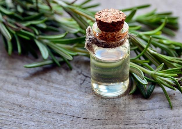 Rosmarinöl in einer glasflasche und rosmarinblättern