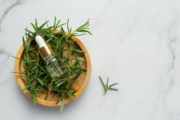 Rosmarinöl in flasche mit rosmarinpflanzen