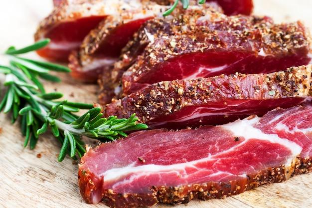 Rosmarinzweig, gewürze und getrocknetes eingelegtes schweinefleisch