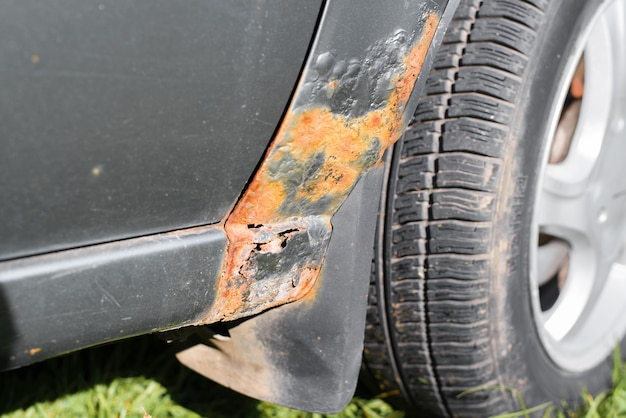 Rost und schäden an der karosserie. metallkorrosion, farbzerfall, löcher im kotflügel, nahaufnahme.