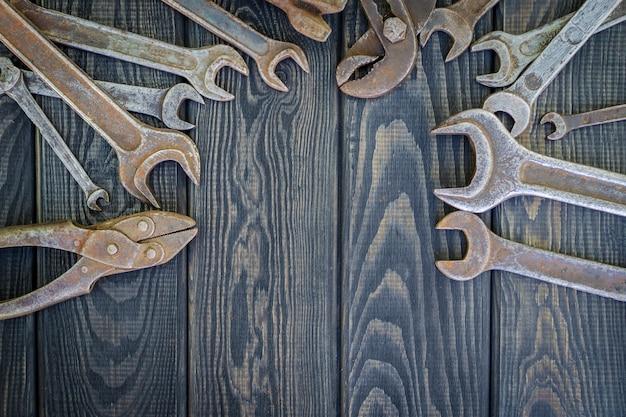 Rostige alte werkzeuge auf schwarzem vintage holzhintergrund