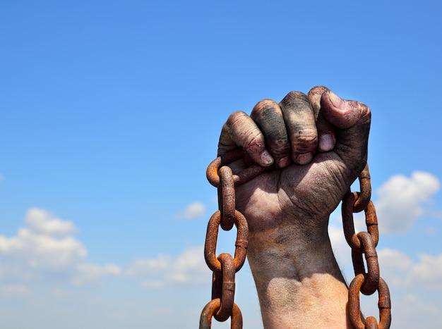 Rostige eisenkette in der menschlichen männlichen rechten hand