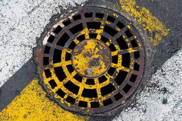 Rostige kanalluke an einem fußgängerüberweg. das konzept der alten kommunikation, die notwendigkeit der reparatur.