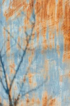 Rostige metalloberfläche in blauer farbe mit einem schatten auf den ästen gemalt. vertikales bild.