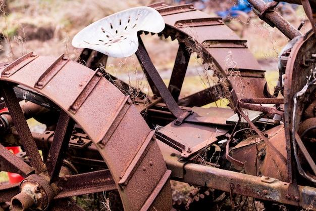 Rostige stahltraktorräder und -sitz beschnitten