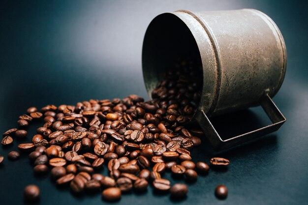 Rostige tasse mit verschütteten kaffeebohnen