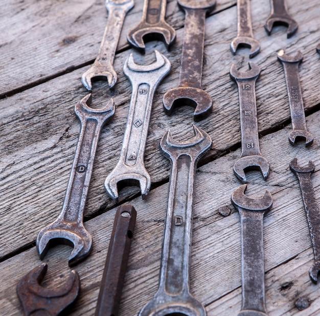 Rostige werkzeuge des metallschlüssels, die auf einem schwarzen holztisch liegen. hammer, meißel, bügelsäge, metallschlüssel