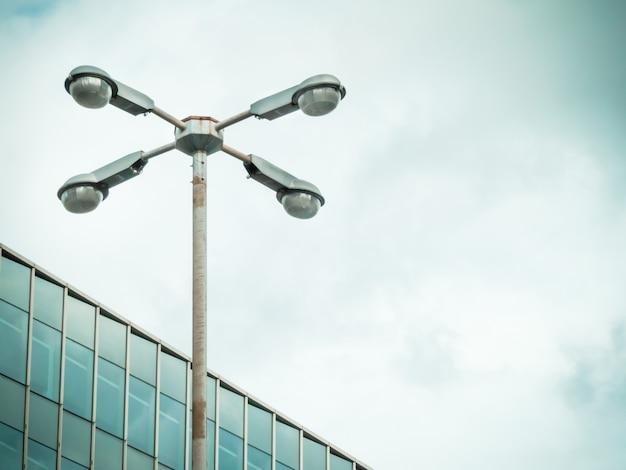 Rostiger mast und leuchtenring mit beleuchtungskörpern.