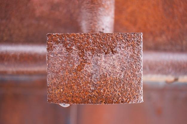 Rostiges nasses metallrechteckige platte in der mitte des rahmens.