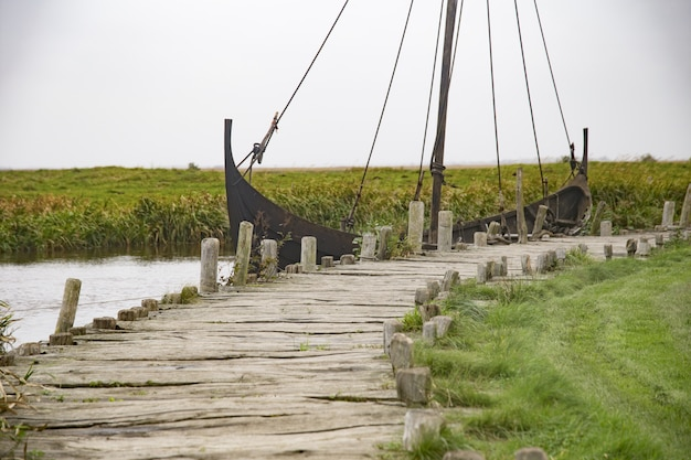Rostiges schiff auf dem see nahe dem hölzernen dock in einem wikingerdorf unter dem klaren himmel