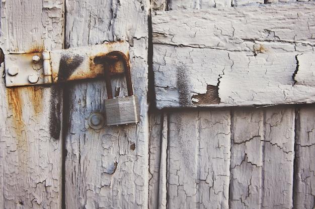 Rostiges vorhängeschloss, das an einem alten weißen holztor hängt