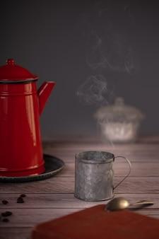 Rot emaillierte kaffeemaschine mit einer metallschale dampfendem kaffee