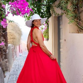 Rot gekleidete frau in einer straße in oia, santorini, griechenland
